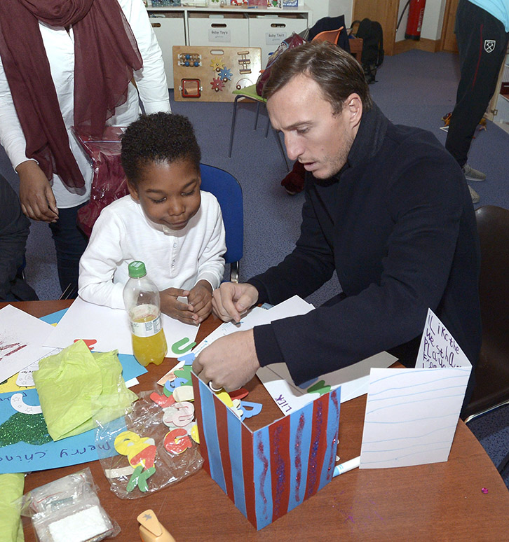 Mark Noble makes Christmas cards with a child at Richard House during the Club's Christmas Visit 2016